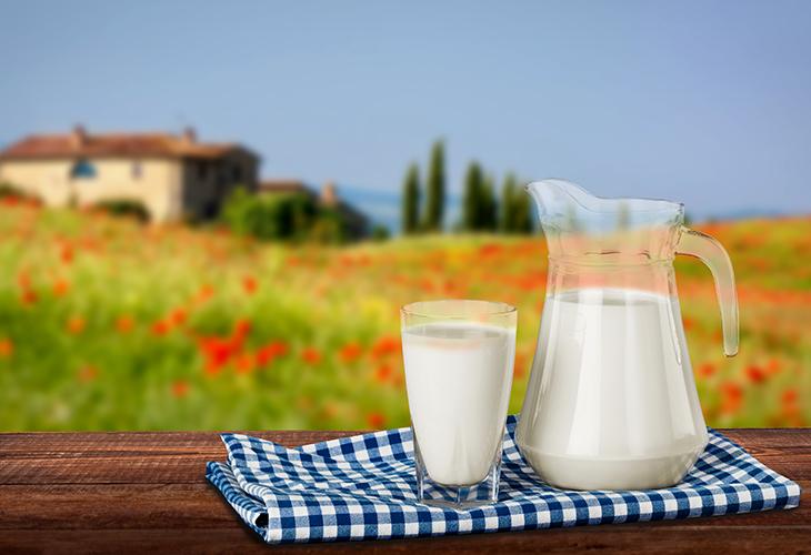 Ein Milchglas und ein Milchkrug, im Hintergrund die Toskana