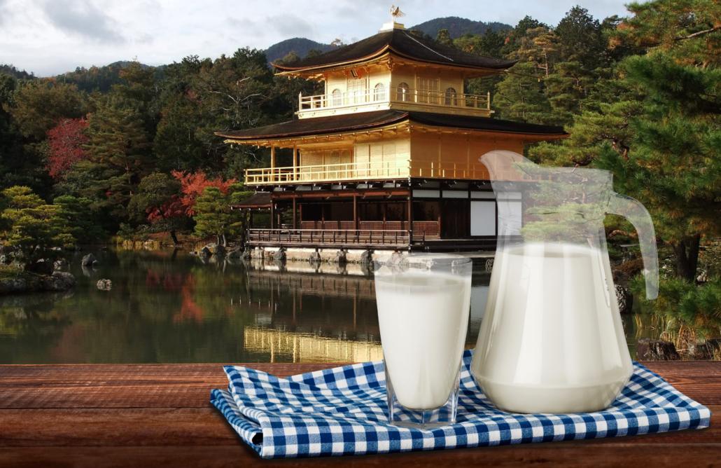 Ein Milchglas und ein Milchkrug, im Hintergrund ein See mit einem typishc asiatischen Gebäude