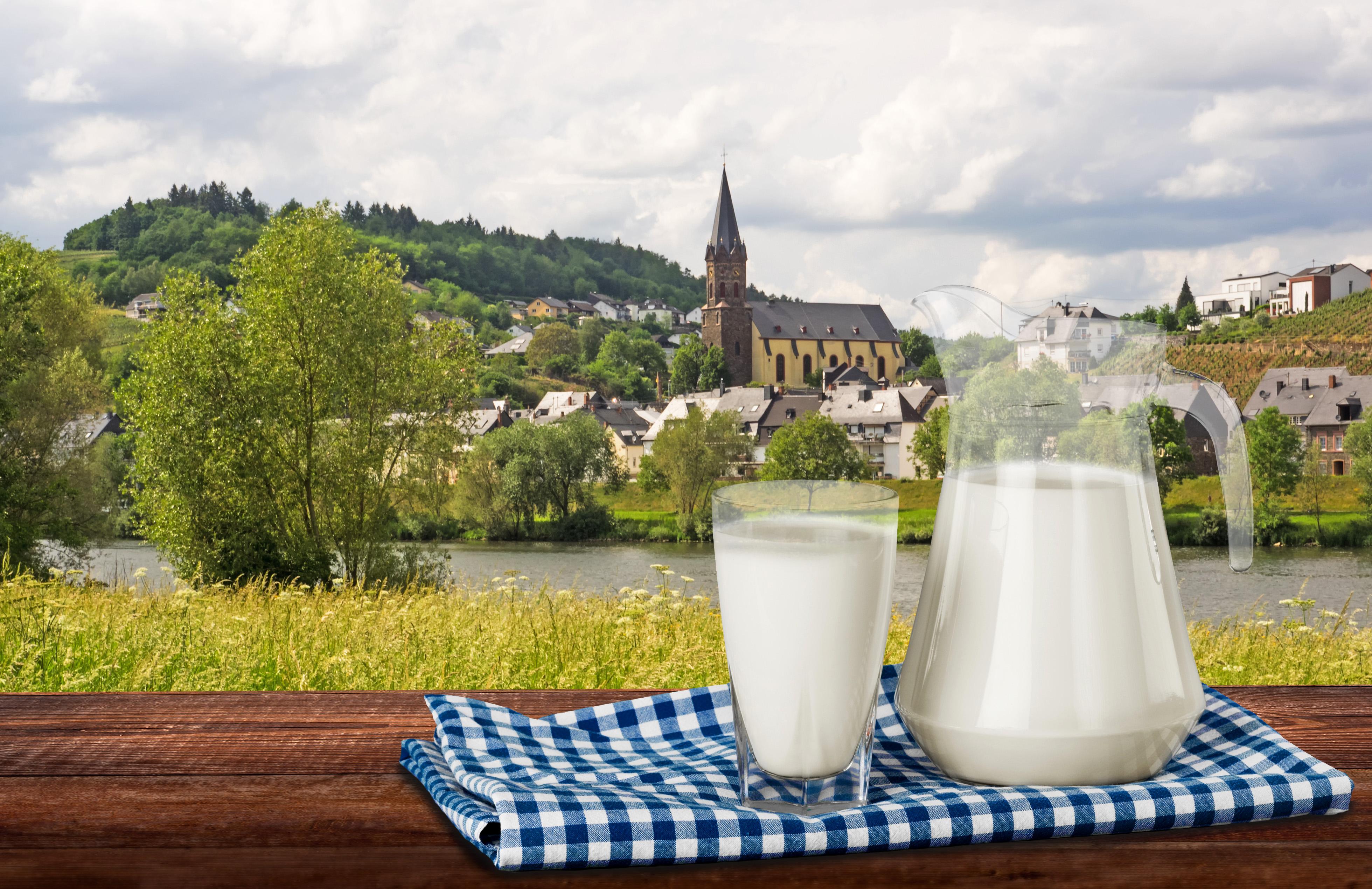 Ein Milchglas und ein Milchkrug, im Hintergrund eine Kirche aus Frankreich