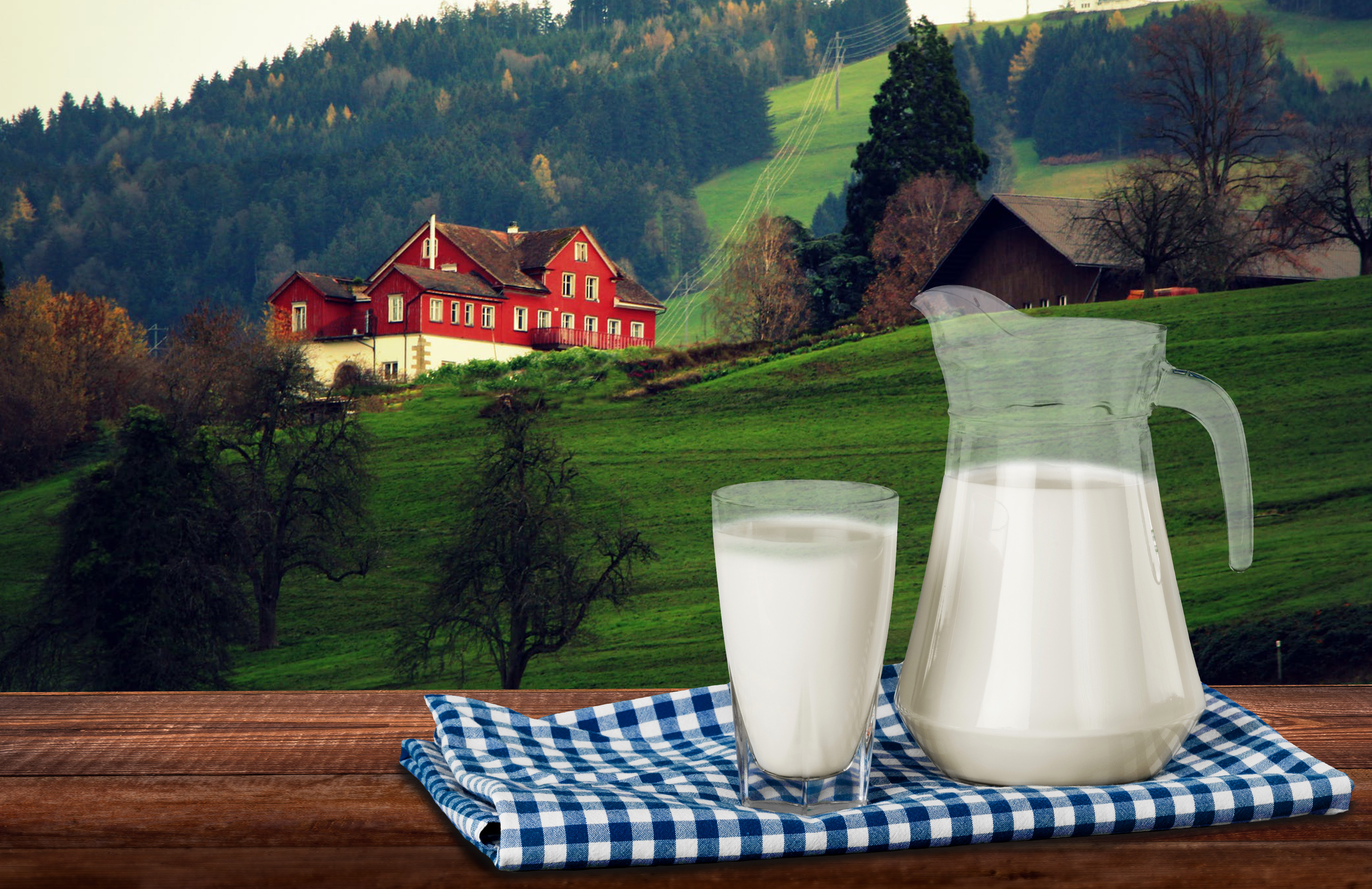 Ein Milchglas und ein Milchkrug, im Hintergrund eine typisch osteuropäische Landschaft mit einem roten Haus.