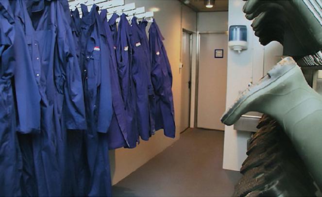 Ein Ankleideraum mit Overalls und Gummistifeln